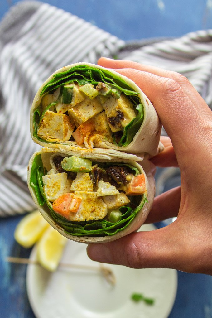 Hand Holding Two Halves of a Curried Tofu Salad Wrap over a Plate