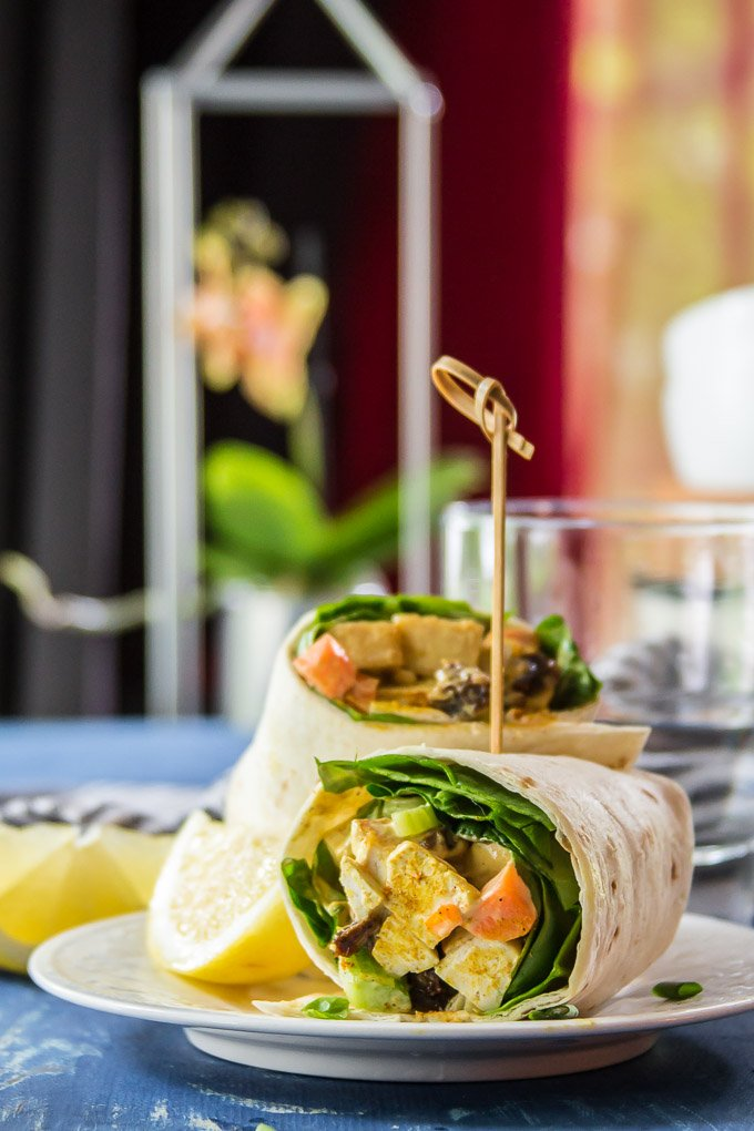 Curried Tofu Salad Wrap Cut in Half on a Plate with Drinking Glass in the Background