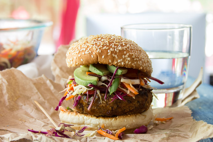 Teriyaki Tempeh Burger Topped with Asian Slaw and Avocado Slices