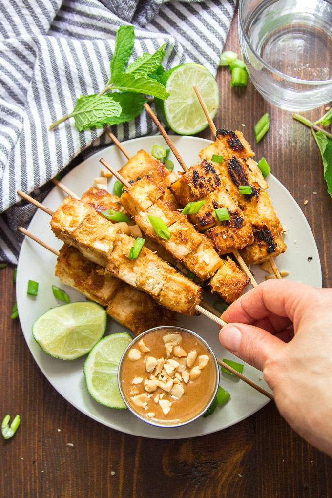 Hand Grabbing a Skewer of Tofu Satay from a Plate