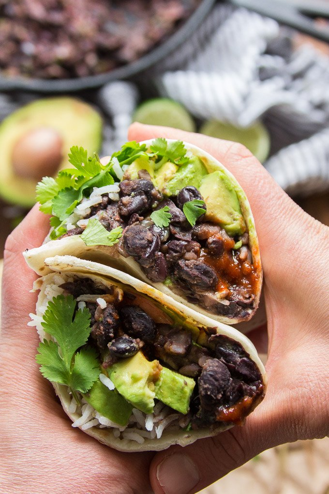 Pair of Hands Holding Two Halves of a Black Bean Burrito