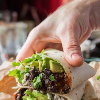 Hand Grabbing Half of a Black Bean Burrito