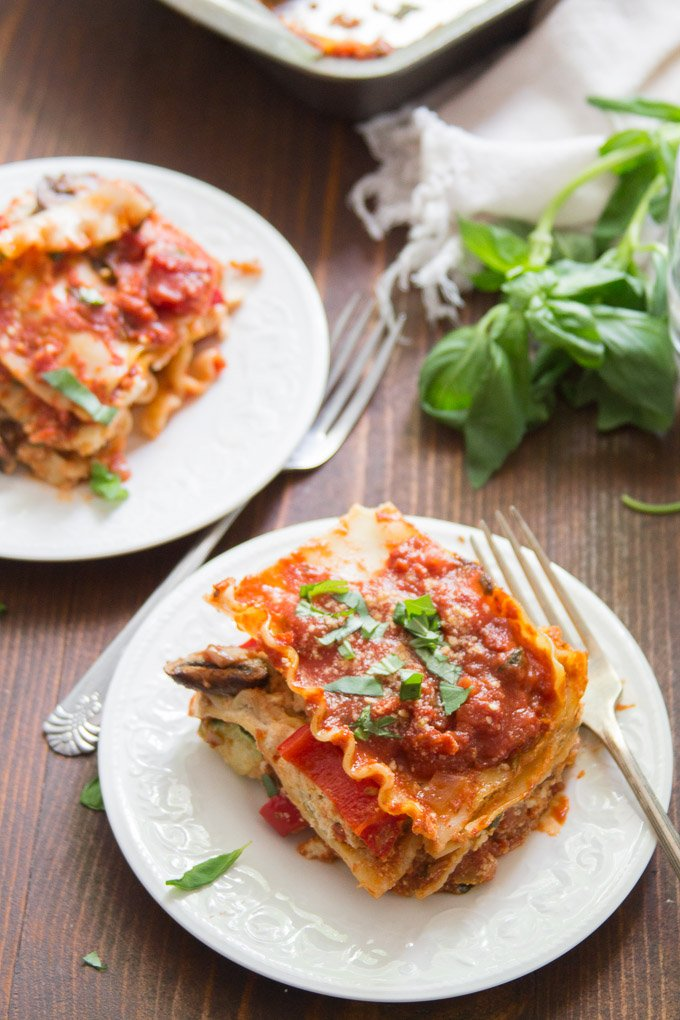 Two Plates of Vegan Lasagna with Fresh Basil in the Background