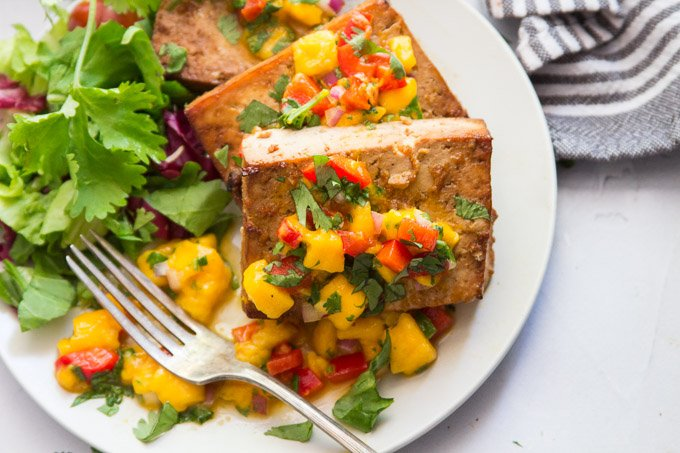 Close Up of Two Slabs of Grilled Tofu Topped with Mango Salsa