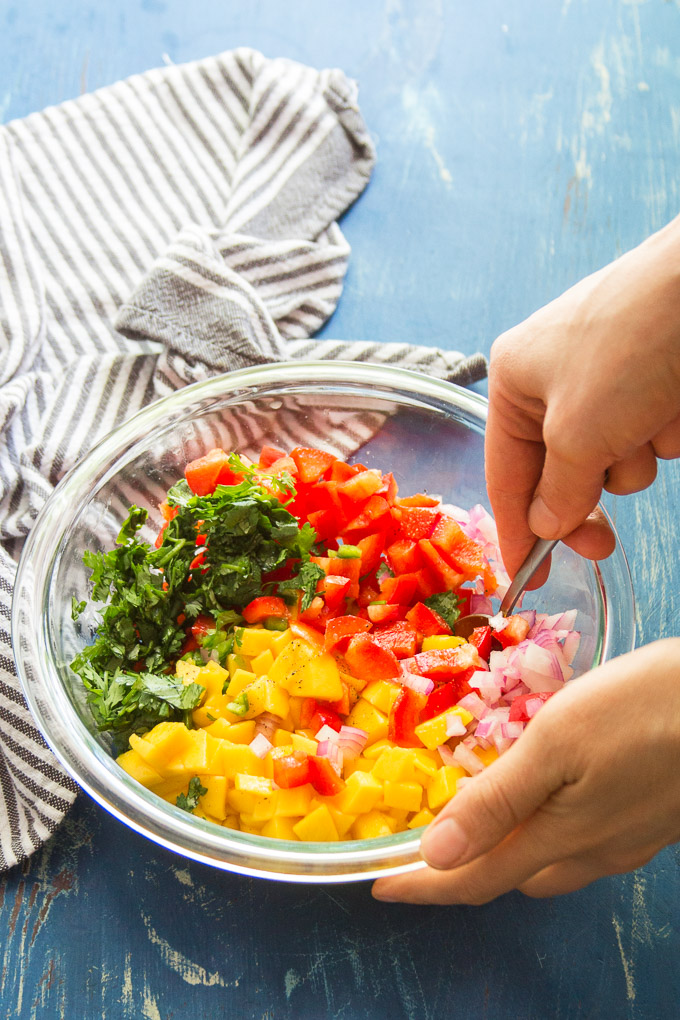 Hand Stirring Mango Salsa Ingredients Together in a Bowl
