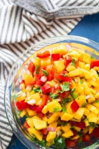 Close Up of a Bowl of Mango Salsa on a Blue Background