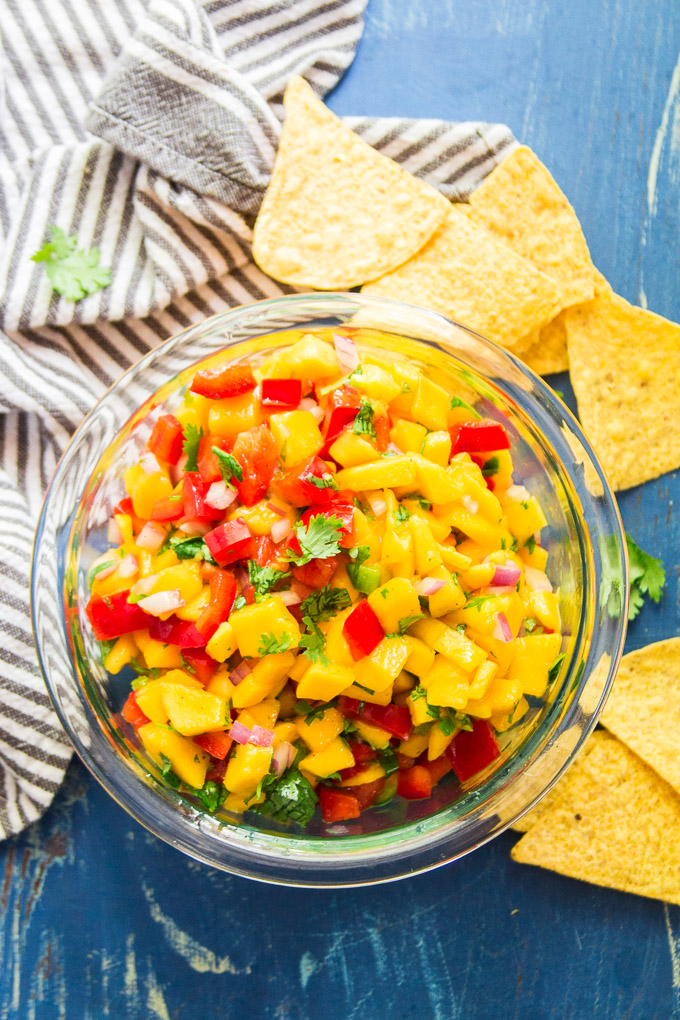 A Bowl of Mango Salsa with Chips and Striped Napkin
