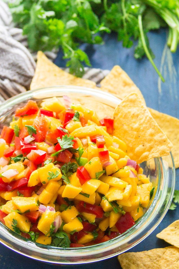 Bowl of Mango Salsa with Chips and Fresh Cilantro in the Background
