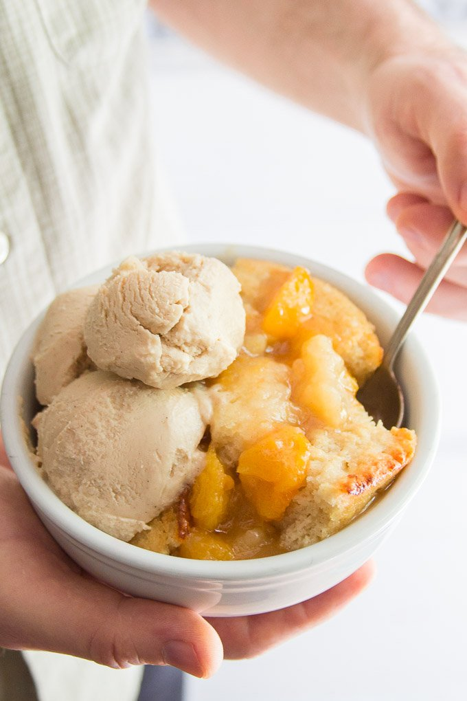 Hands Holding a Spoon and Bowl of Vegan Peach Cobbler Topped with a Scoop of Vegan Vanilla Ice Cream
