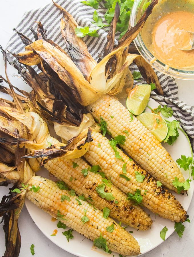 4 Ears of Mexican Grilled Corn on a Plate with Lime Wedges and Sauce on the Side