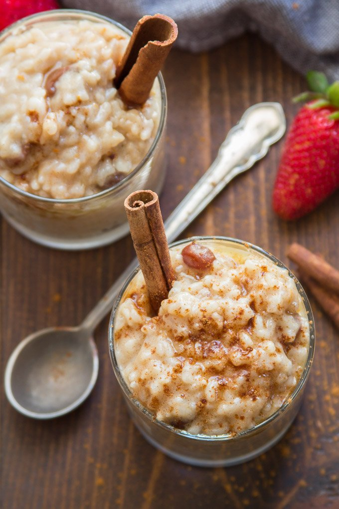 Two Glasses of Vegan Rice Pudding with Cinnamon Sticks and Strawberries