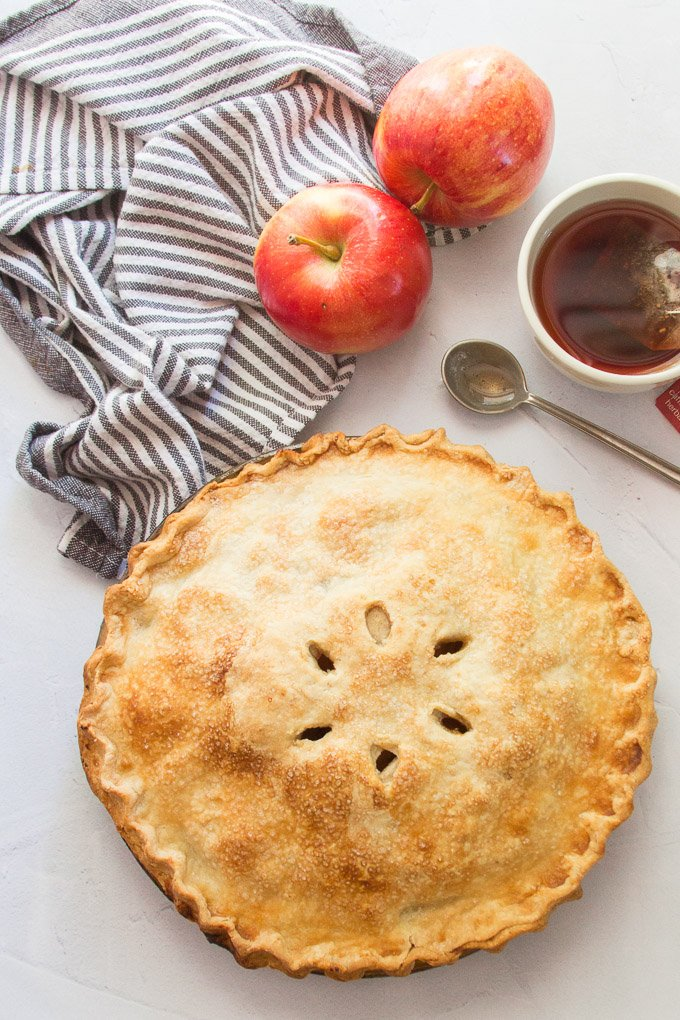 A Whole Vegan Apple Pie on a Table with Napkin, Apples, and Coffee Cup
