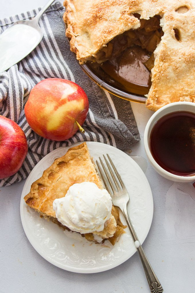 A Slice of Vegan Apple Pie on a Plate with Apples, Napkin, and Coffee Cup