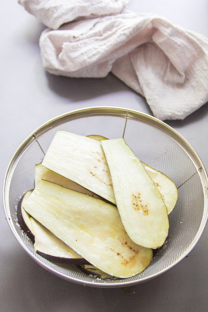 Eggplant Slices Being Salted in a Colander