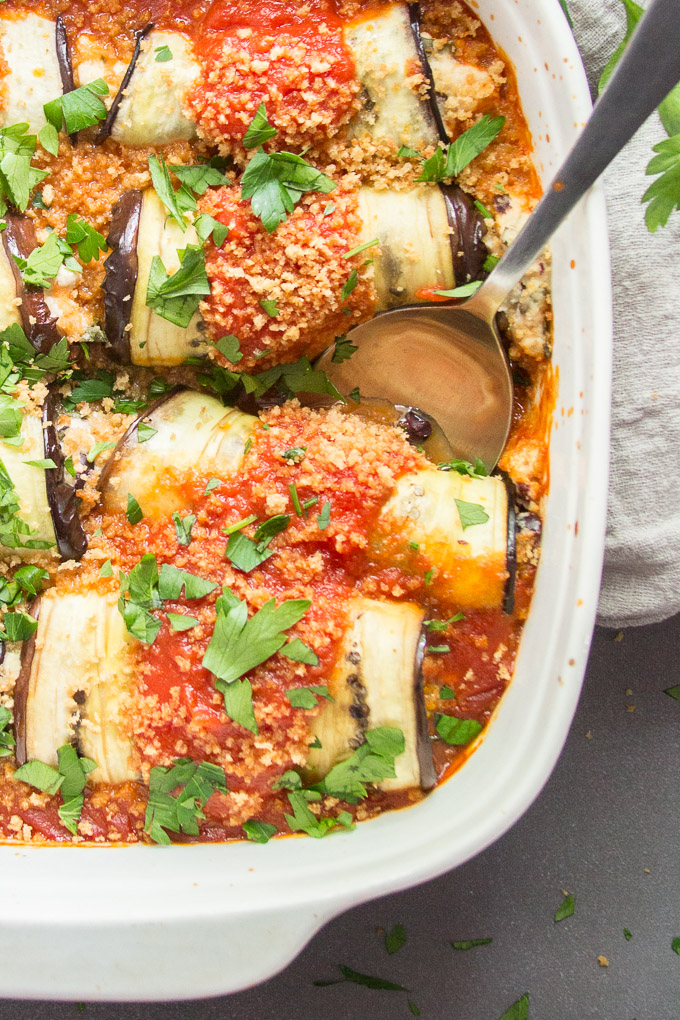 Vegan Eggplant Rollatini in a Casserole Dish with Serving Spoon
