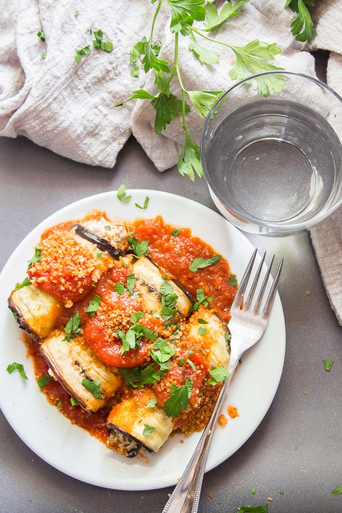 Vegan Eggplant Rollatini on a Plate with Fork, Water, Glass and Napkin