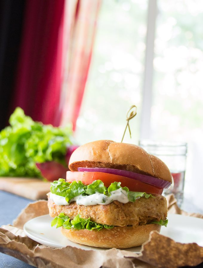 """Crispy Tofu """"Fish"""" Sandwich with Lettuce, Tomato and Onion on a Plate with Water Glass in the Background"""