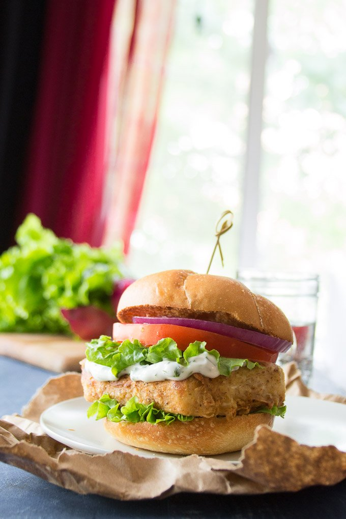 "Crispy Tofu ""Fish"" Sandwich with Lettuce, Tomato and Onion on a Plate with Water Glass in the Background"
