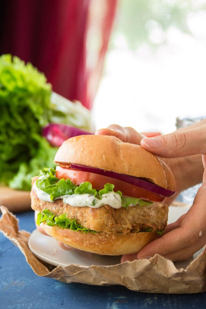 Hands Holding a Vegan Fish Fillet Sandwich Over a Plate