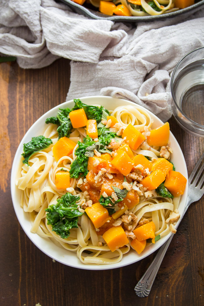 Bowl of Butternut Squash Pasta with Fork and Drinking Glass