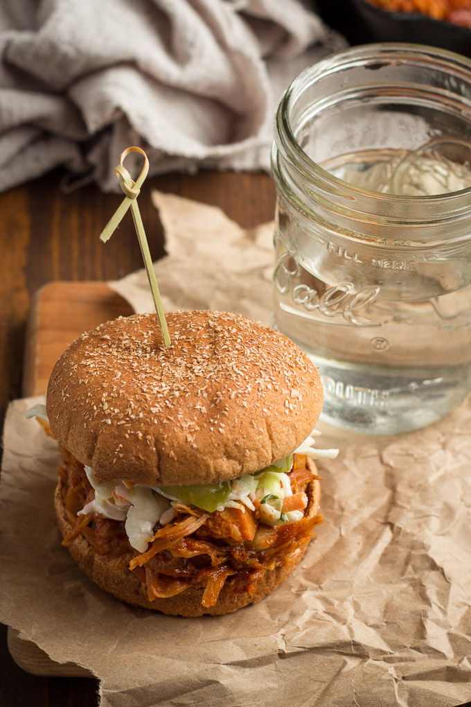 Jackfruit Pulled Pork Sandwich on a Paper Wrapper with a Glass of Water