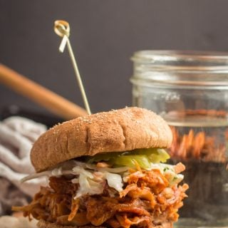 Jackfruit Pulled Pork Sandwich with a Water Glass and Skillet in the Background