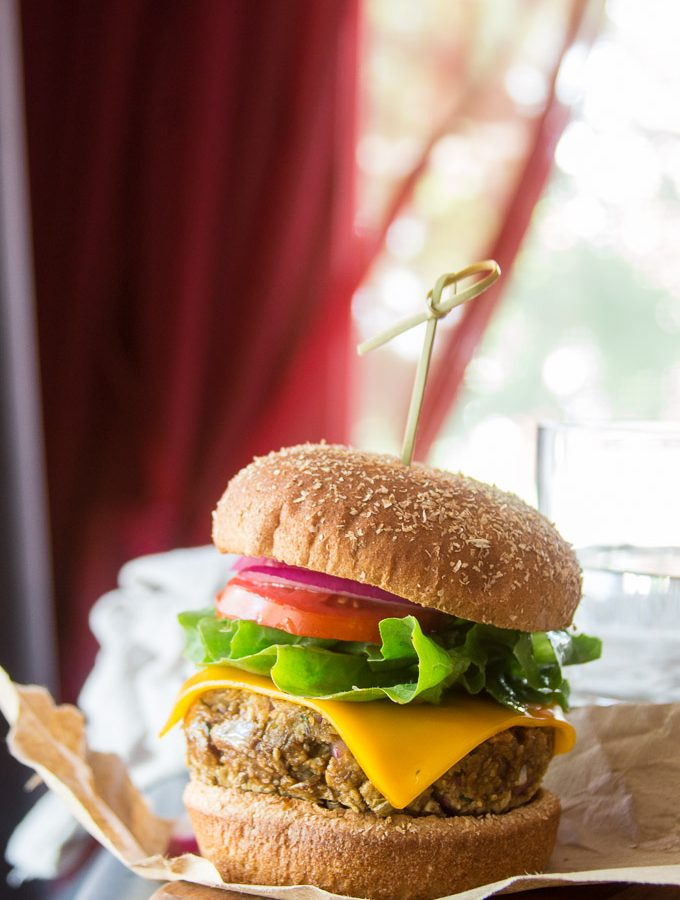 Lentil Burger on a Bun with Toppings and Water Glass in the Background