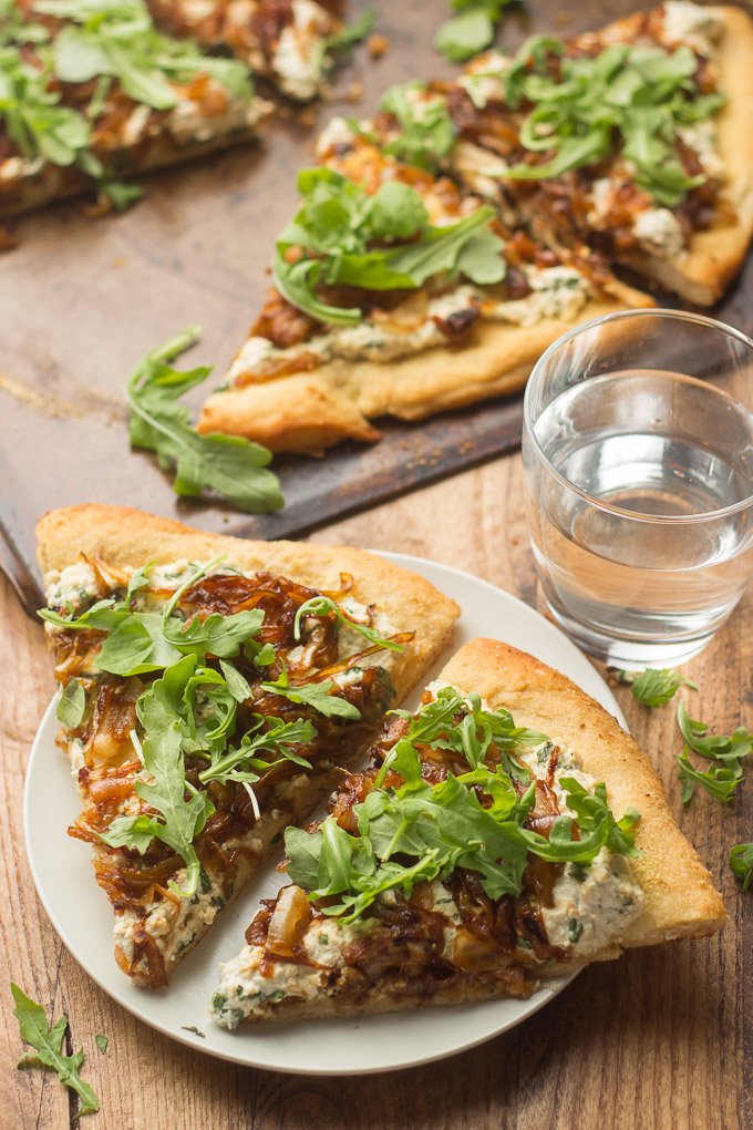 Two Slices of Caramelized Onion Pizza on a Plate with a Baking Dish on the Background