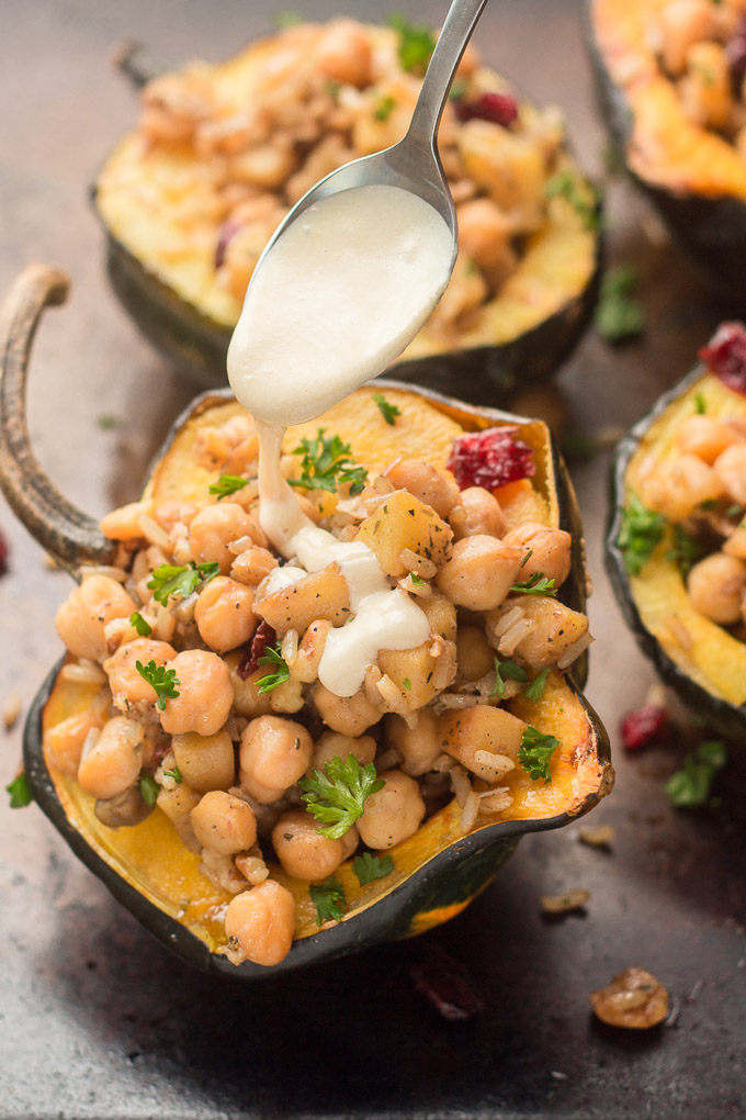 Spoon Drizzling Tahini Dressing on a Stuffed Acorn Squash