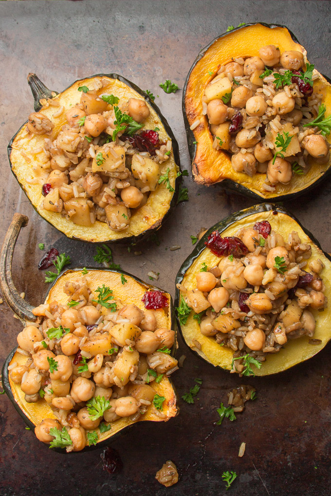 Four Stuffed Acorn Squash Halves on a Baking Sheet