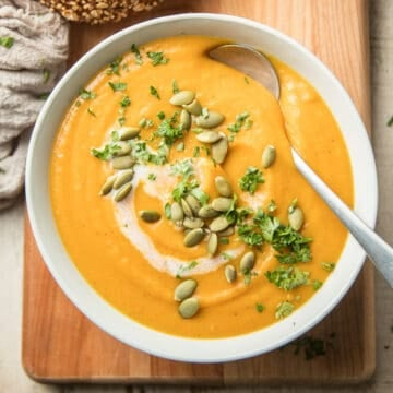 Bowl of Vegan Butternut Squash Soup on a Wooden Surface with Bread on the Side.