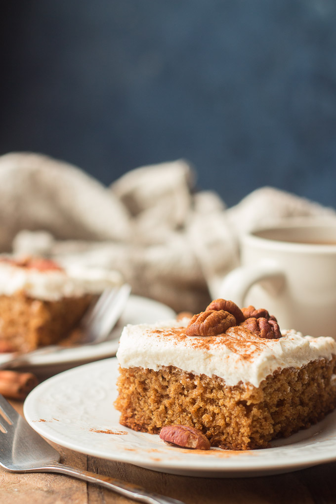 Close Up of a Slice of Spice Cake with Coffee Cup and a Second Slice in the Backgroun