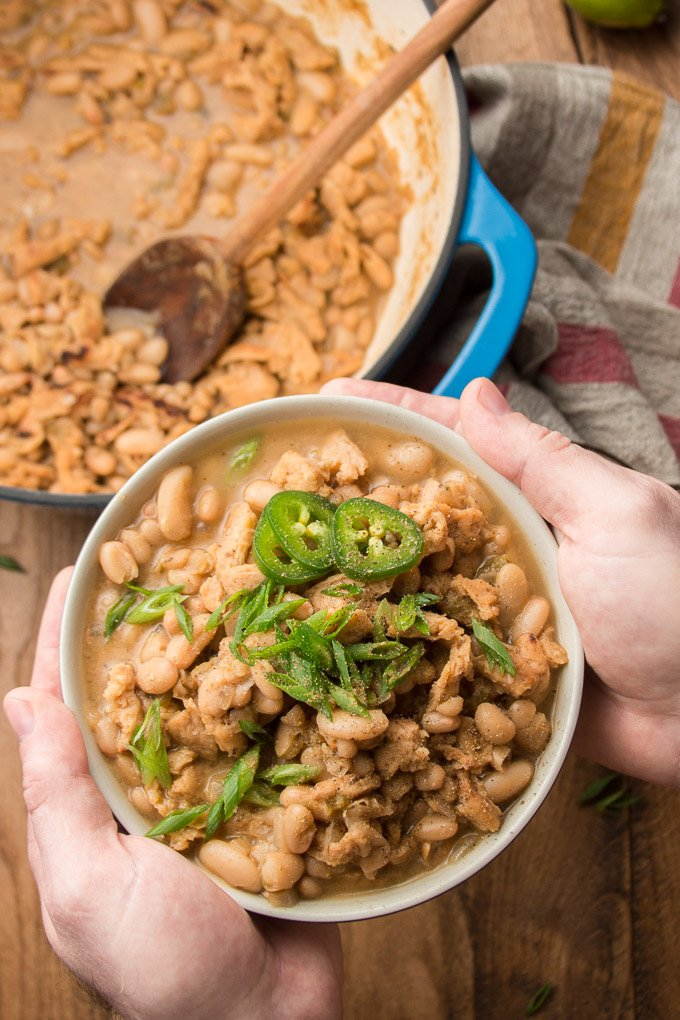 Pair of Hands Holding a Bowl of Vegan White Chili Over a Table