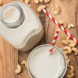Glass and Bottle of Cashew Milk on a Wooden Table with Cashews