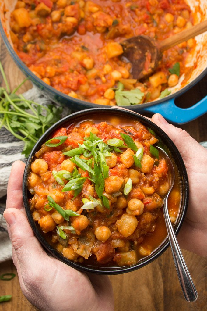 Pair of Hands Holding a Bowl of Chickpea Stew Over a Table
