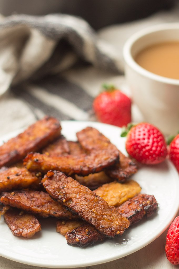 Close Up of Tempeh Bacon Slices on a Plate with Strawberries and Coffee Cup in the Background