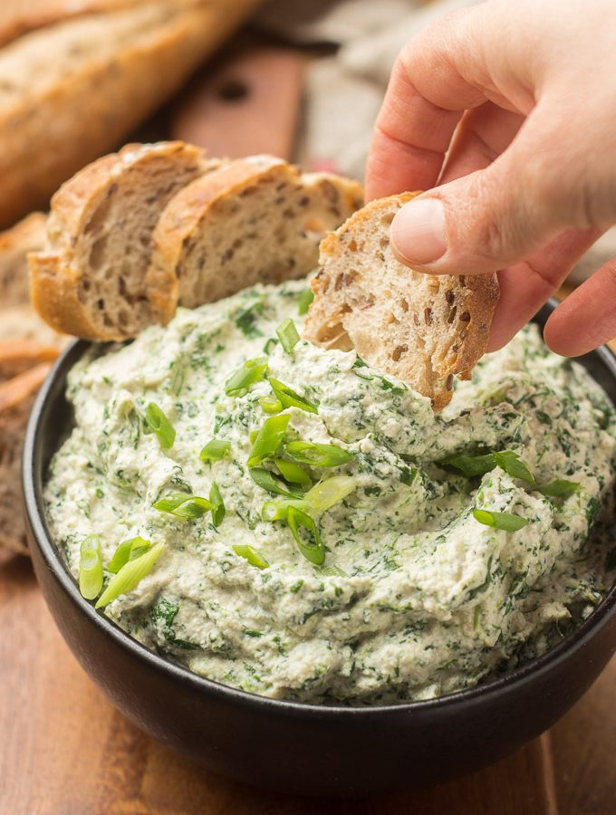 Hand Dipping Bread into a Bowl of Vegan Spinach Dip