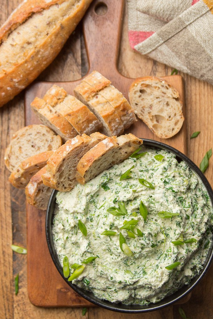 Bowl of Vegan Spinach Dip on a Wooden Serving Board Surrounded with Bread Slices