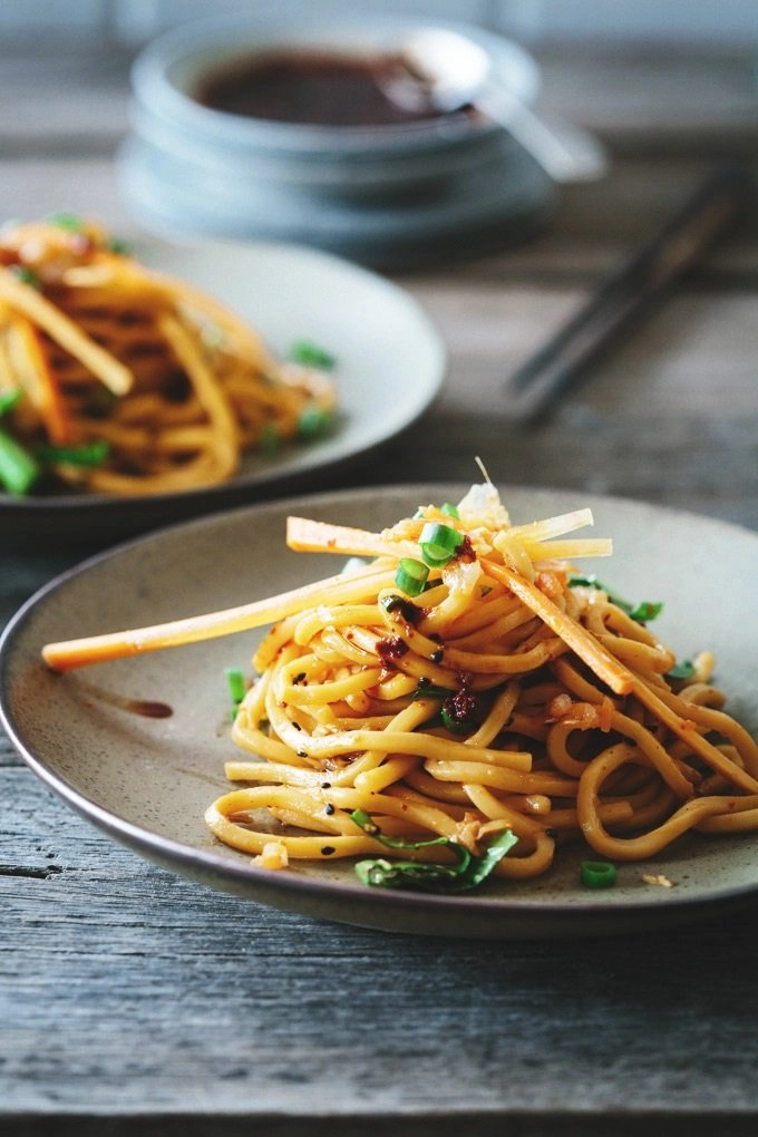 Two Plates on Kimchi Noodle Salad on a Wooden Table