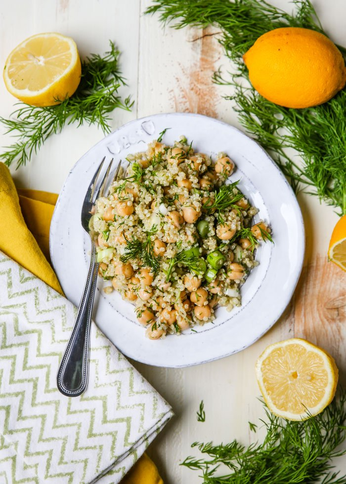Lemon Dill Quinoa Chickpea Salad on a Plate with Fork Surrounded By Lemon Halves and Fresh Dill