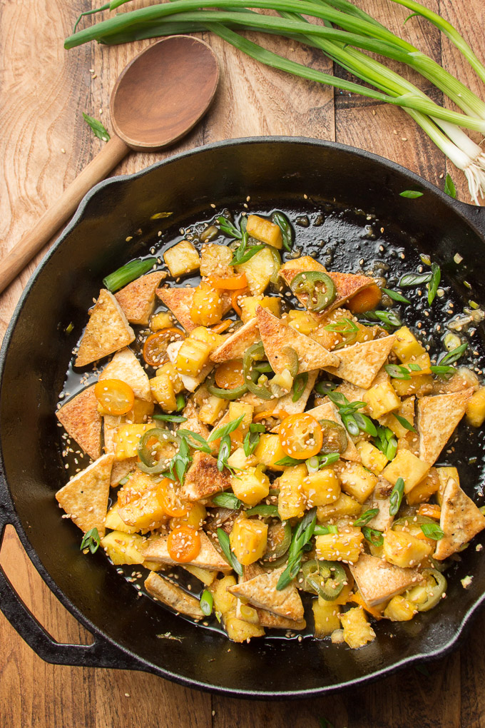 Cast Iron Skillet Filled with Spicy Tofu & Pineapple Stir-Fry on a Wooden Table