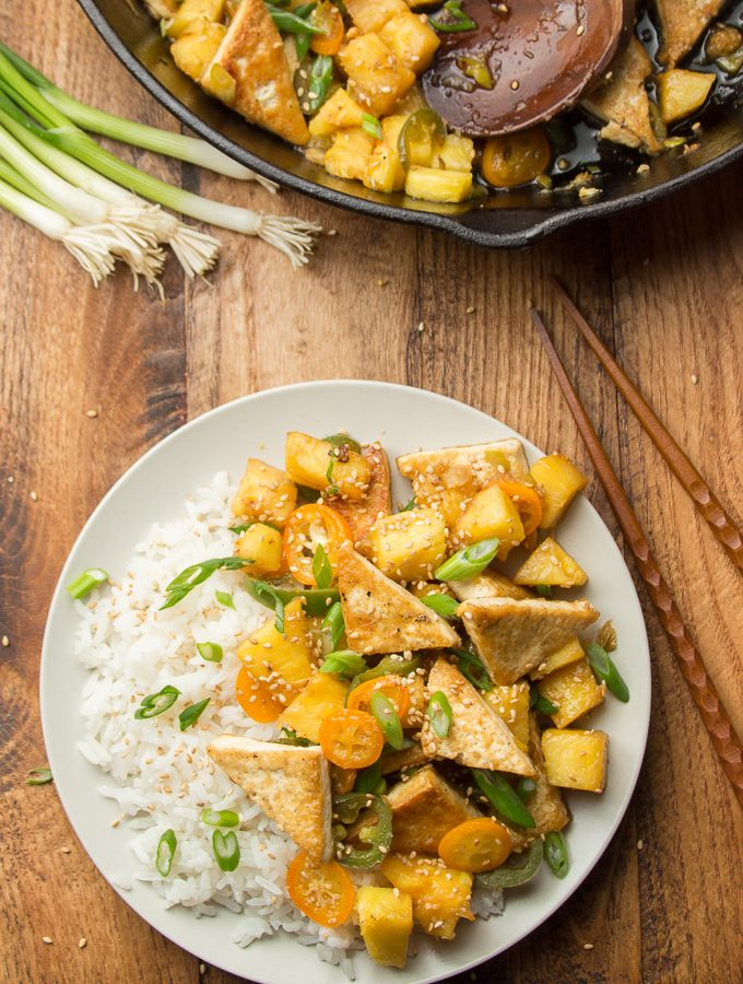 Table Set with a Skillet, Bunch of Scallions and Plate of Spicy Tofu & Pineapple Stir-Fry
