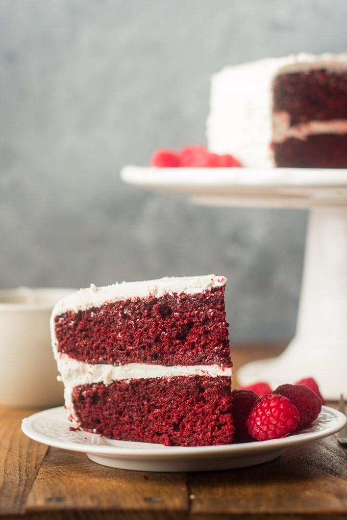 Slice of Vegan Red Velvet Cake on a Plate with Raspberries