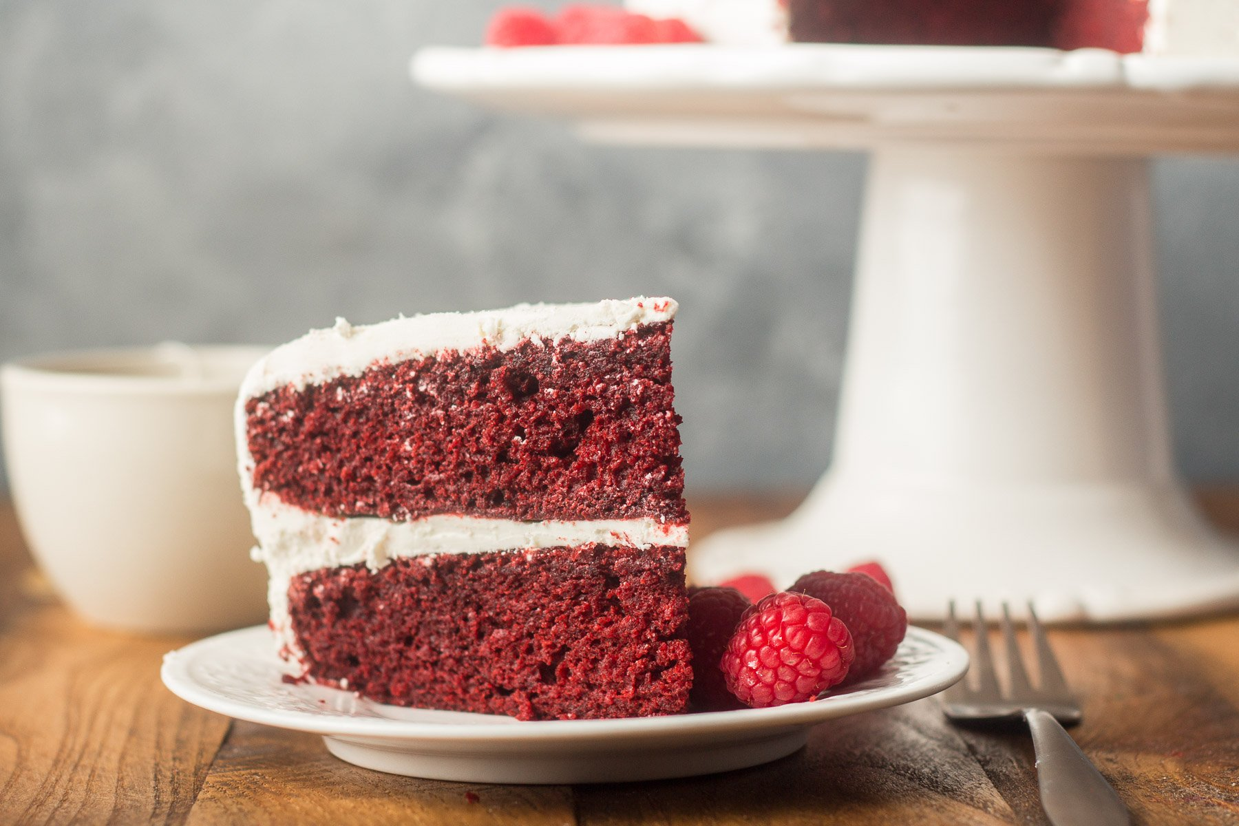 Slice of Vegan Red Velvet Cake on a Plate with Raspberries