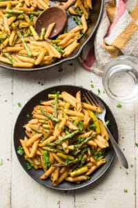 Table Set with Plate of Balsamic Asparagus Pasta, Skillet, Fork, and Water Glass