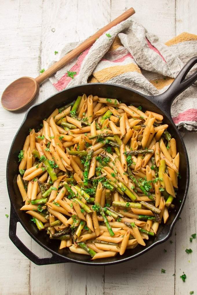 Skillet of Balsamic Asparagus Pasta on a White Wooden Surface with Tea Towel and Wooden Spoon