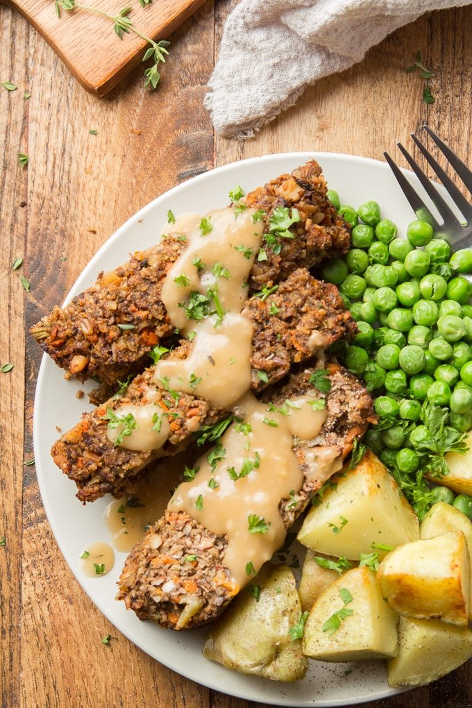 Close Up of Nut Roast on a Plate with Gravy, Peas and Potatoes