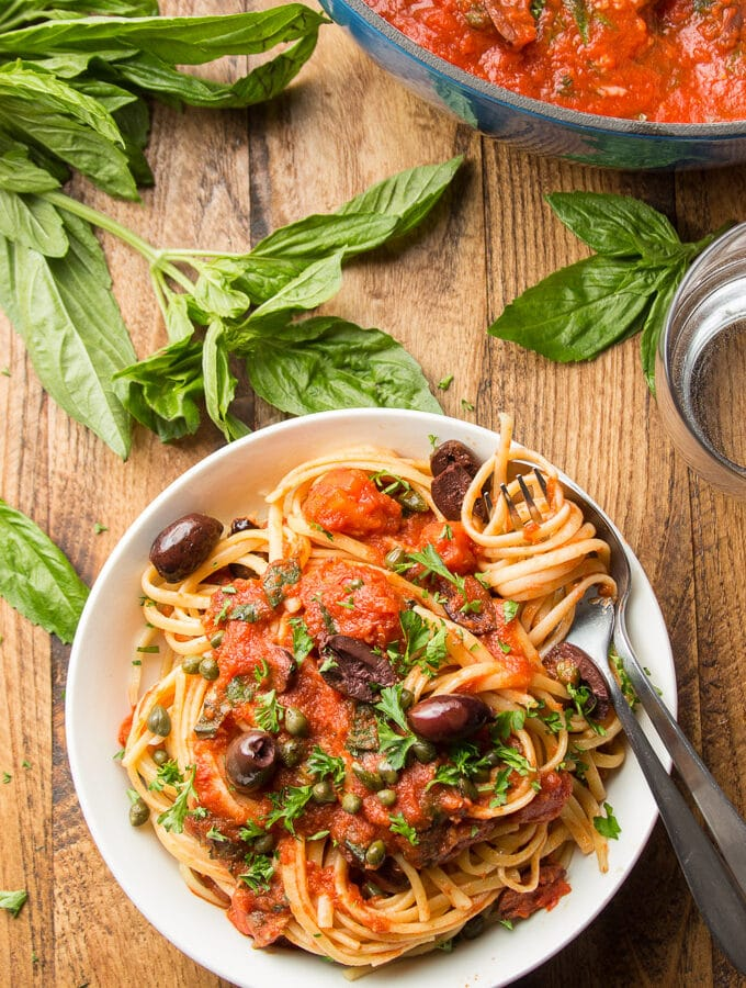 Bowl of Linguine Puttanesca with a Clump of Pasta Wrapped Around a Fork