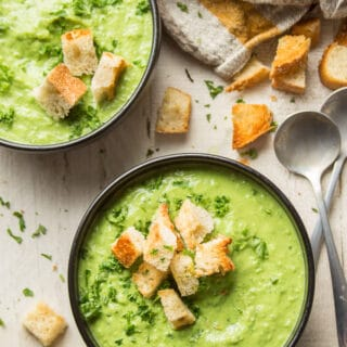 Two Bowls of Fresh Pea Soup on a White Wooden Table with Spoons