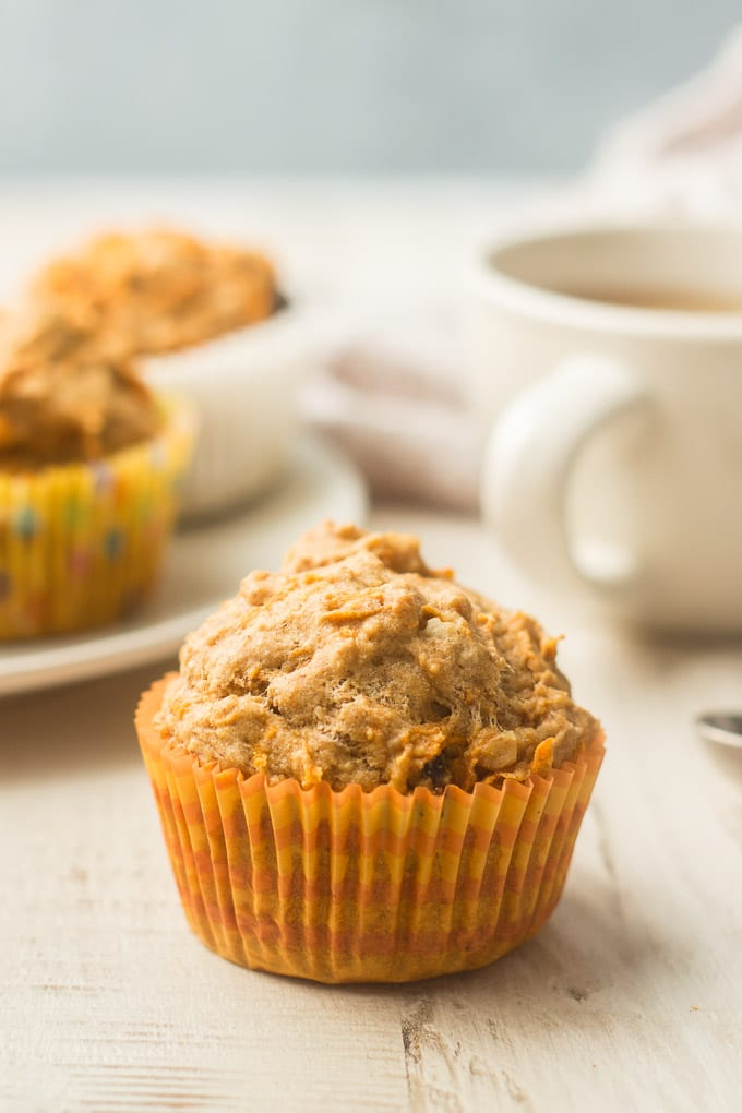 Close Up of a Vegan Carrot Muffin with Tea Cup and Plate of Muffins in the Background